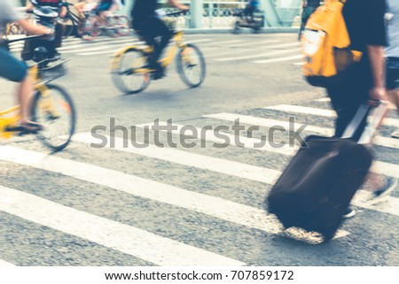unrecognized pedestrain with suitcase crossing road and people riding public bicycles,Tianjin city,China. #707859172