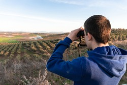 Unrecognized young boy standing in the mountain looking the landscape using binoculars.