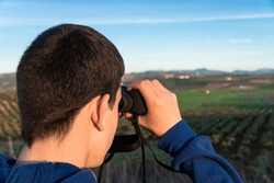 Unrecognized young boy standing in the mountain looking the landscape using binoculars. Selective focus.