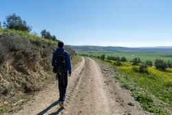 Unrecognized young boy wearing sports clothes and backpack walking in the countryside.