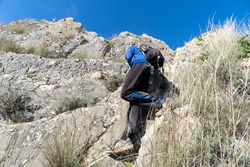 Unrecognized young boy wearing sportswear climbing the mountain during sunny day.