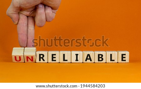 Unreliable or reliable symbol. Businessman turns wooden cubes and changes the word unreliable to reliable. Beautiful orange background, copy space. Business and unreliable or reliable concept. Photo stock ©