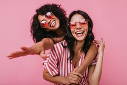 Unrestrained merriment of two girls captured on snapshot. Photos in pink shades of brunettes with beautiful curls, embracing in friendly way