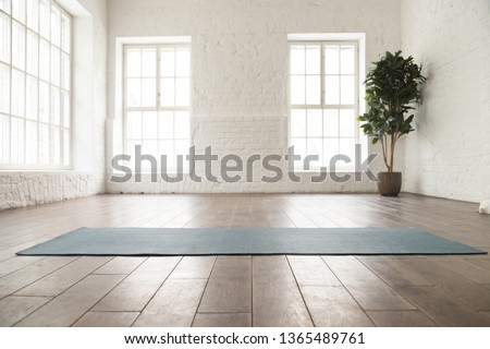 Unrolled yoga mat on wooden floor in modern fitness center or at home with big windows and white brick walls, comfortable space for doing sport exercises, meditating, yoga equipment