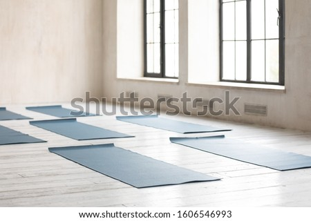 Unrolled yoga mats on wooden floor in fitness center with nobody, modern class prepared for group working out, comfortable space for doing sport exercises, empty class room with big windows