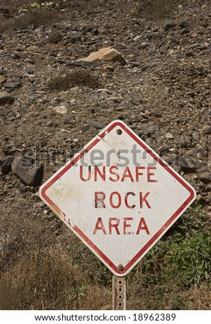 Unsafe rock area sign at the bottom of a steep hill