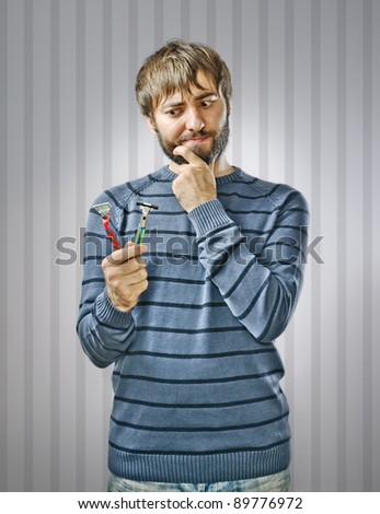 Unshaved Young Man Choosing between Two Razors