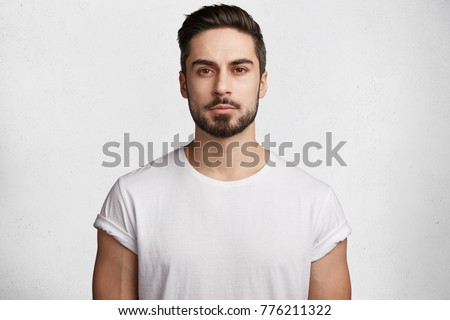 Unshaven confident serious young male enterpreneur with attractive appearance dressed casually as spends weekends at home, isolated over white concrete background. Stylish handsome guy indoor