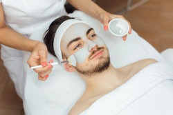 Unshaven man having cosmetic mask care in spa salon, side, top view - Image