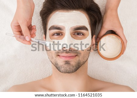 Unshaven man having cosmetic mask in spa salon, top view