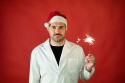 Unshaven sleepy doctor with Santa Claus hat Celebrating Christmas or New Year on duty holds Burning sparklers on red studio copy space. Merry Christmas and Happy New Year for healthcare professionals