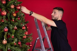 Unshaven young man in black T-shirt hanging toy balls on Christmas tree using ladder on studio red backdrop. Christmas vacation quarantine alone. self-gifter concept. decorate Christmas tree yourself