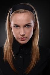 Unsmiling teenager wearing black looking at camera.