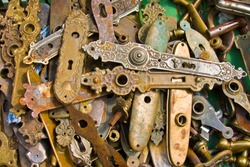 Unsorted pile of old, historic an vintage escutcheons made of bronze and of other metals to cover a door latch.