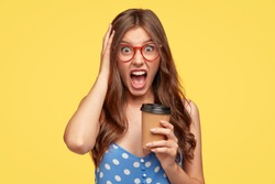 Unsound angry student shouts at her boyfriend during coffee break, holds paper disposable cup with beverage, keeps jaw dropped, exclaims in irritation, dressed in polka dot blouse. Negative feeling