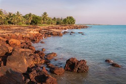 Unspoiled beach at sunset time. Rocky landscape, green trees and palm trees. Coastline of Timor sea. No people in the picture. Dundee Beach. Northern Territory NT, Australia