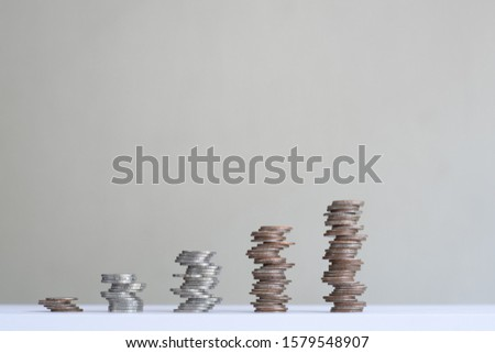 Unstable coin stacks arranged into growth chart on white background, finance and business concept, copy space