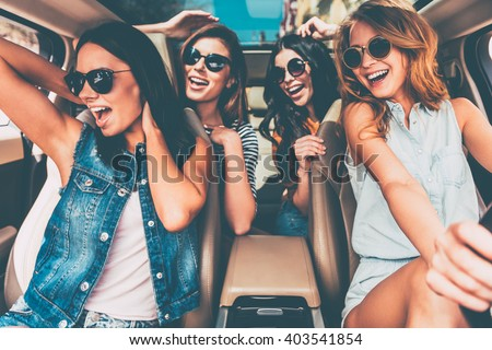 Unstoppable beauties. Four beautiful young cheerful women looking happy and playful while sitting in car