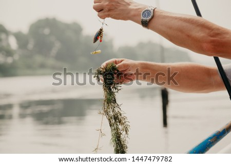 Unsuccessful catch. Hand shoots green river algae that are hooked onto the hook of a fisherman's fishing pole above the water surface. #1447479782