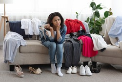 Unsuccessful Online Shopping. Disappointed Pensive Black Woman Sitting On Couch Beside Piles Of Unfitting Clothes And Shoes Ordered In Internet