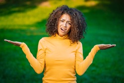 Unsure african american woman shrugs her arms, makes gesture of I don't know, care, can't help anything . Mixed race lady on green grass background