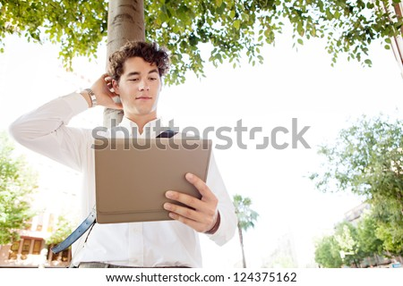 Unsure businessman scratching his head while using a tablet device, standing in a wide city avenue with trees, outdoors.