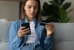 Unsuspecting young lady dubious web shop client making purchase at internet giving personal data to fraudulent scam website using cell. Soft focus on woman hands with modern mobile phone and bank card