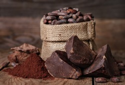 unsweetened baking block chocolate, Cocoa powder and cocoa beans on old wooden background