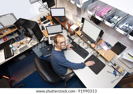 Untidy computer repair shop, with an IT technician working on several computers at the same time