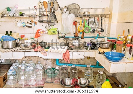 Untidy Kitchenware ; Pile of dirty dishes in sink and gallon water under the counter in the kitchen