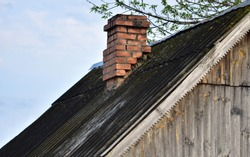 Untidy old lid of an abandoned house with terracotta brick chimney