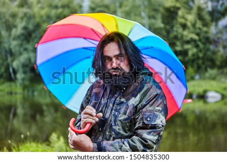 Untidy shaggy man, 53 years old, with a painted beard and pouting lips, hides from the rain under a rainbow umbrella, portrait against the background of wild nature with a river and forest. #1504835300