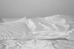 Untidy Silk Bedding, Showing a Textile Pillow Edge with Sheets of a scruffy Appearance of the Polyester with Creasing and Folds to the Luxurious Material.