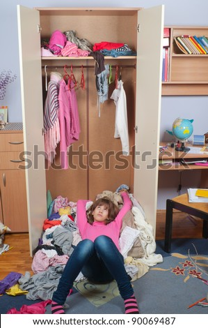 Untidy teenage girl lying on pile of wrinkled clothes inside her wardrobe and daydreaming