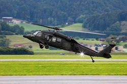 Untitled military helicopter flying. Army helicopter with no markings. Air force. Heli with mountain background.