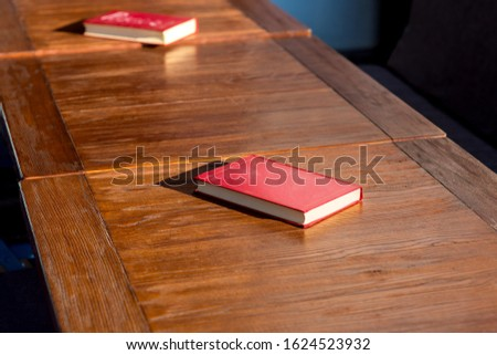 Untitled red hardcover book on a wooden brown table lit by the sunlight of a empty street cafe, nobody closeup.
