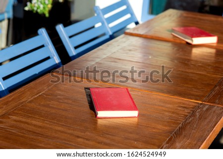 Untitled red hardcover book on a wooden brown table with blue chairs lit by the sunlight of a empty street cafe, nobody closeup.
