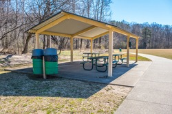 Unused and empty picnic area under a pavilion with garbage cans and several tables in a park on a sunny day in late winter