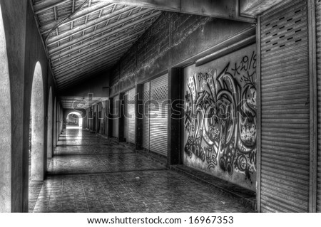 Unused row of retail outlets with graffiti - stock photo