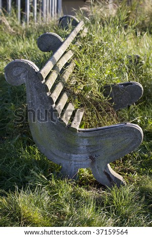 Unused sitting bench fallen to disrepair, tall grass growing over
