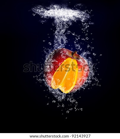 Unusual And Unique Image Of An Apple With A Orange Centre, Diving Underwater Into A Pool Of Water In Healthy Eating Concept Titled A Splash Of Difference - stock photo