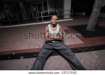 Unusual angle of a man sitting on the curb with arms crossed