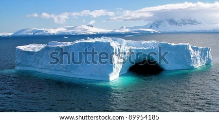 Unusual Antarctic iceberg in blue colours with coast and ocean during summer