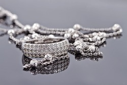 Unusual beautiful silver chain and a silver ring with gems on the reflecting surface