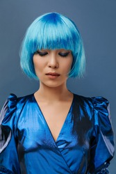 Unusual charming asian lady with short hair, modern makeup and blue gorgeous birth dress posing with closed eyes on isolated background..
