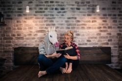 Unusual couple reading a book in stylish apartment. Attentive girl sits on bed with funny man in comical mask. Young woman with strange boyfriend at home.