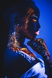 unusual fluorescent makeup on african woman's skin glowing under ultraviolet light. mysterious woman with UV painting on her body. body art