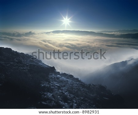 Unusual high mountain view of a sunrise over foggy valleys.