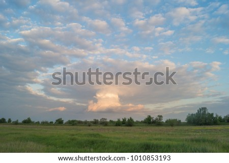 Unusual interesting clouds in the blue sky above the green field with trees #1010853193