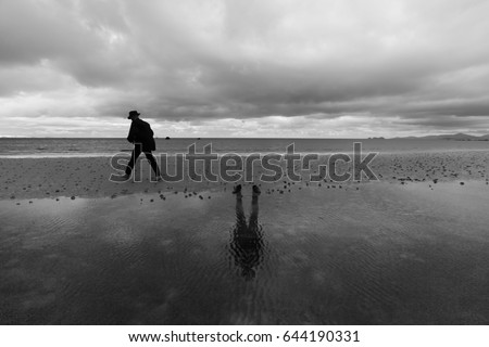 unusual man on beach black and white with reflection